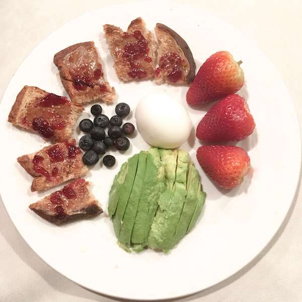 A plate of mini toasts, blueberries, eggs, avocado, and strawberries