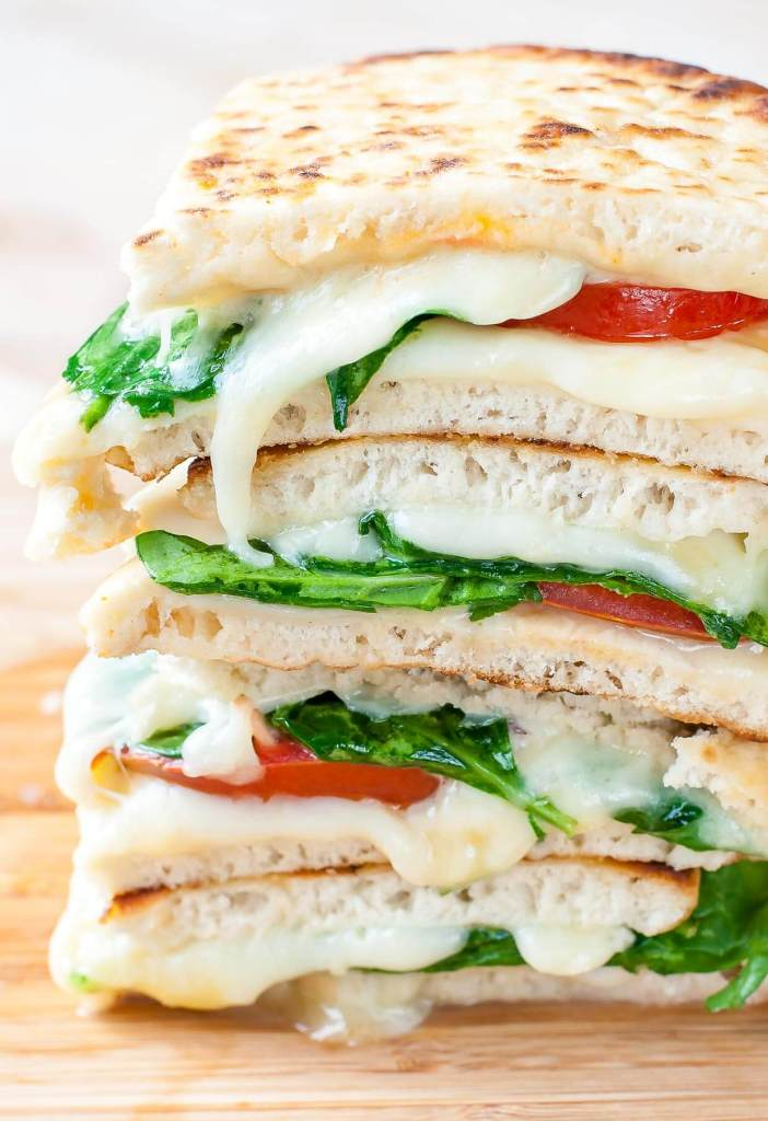 There are pitas piled on top of each other with slices of spinach, cheese and tomatoes in between.