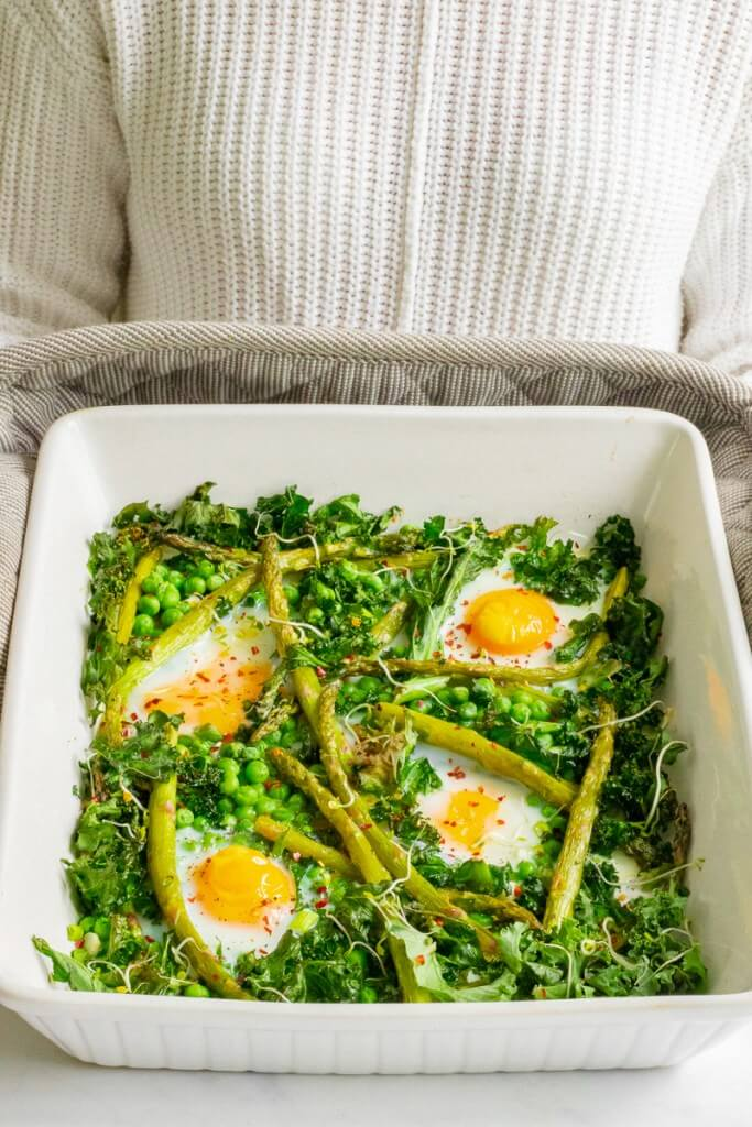 A breakfast tray filled with baked greens and eggs.