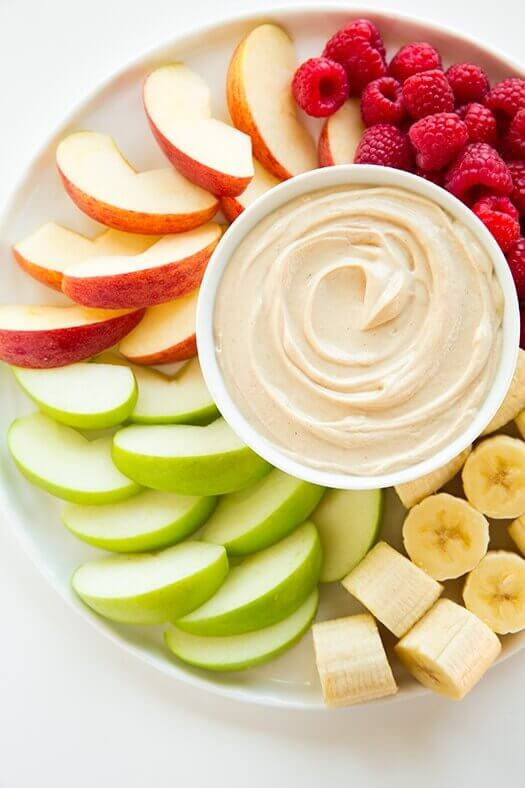 Peanut butter fruit dip with apples, bananas, and raspberries