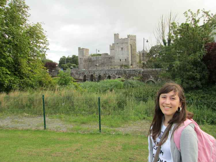 Young woman with a backpack and a castle on the background.