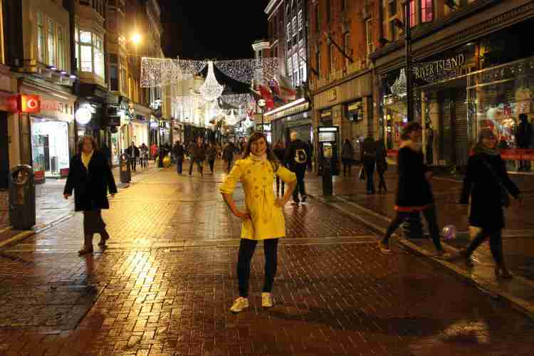 Woman standing on a busy street at night, Christmas lights hanging.