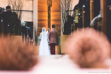 Inside of a church, something brown out of focus on the first plain, couple getting married on the background.