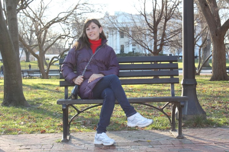A young woman sitting on a bench in a square in winter in front of the White House.