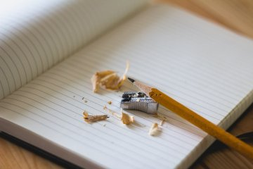 An open notebook with blank pages, a pencil and a sharpener on it.
