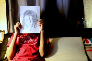 19 year old Cory Levy of Bushwick, Brooklyn holds a self-portrait in front of his face. While sitting in his room, he expresses feeling invisible and preferring it that way. 11/8/13 Photo by Gabrielle A. Wright.