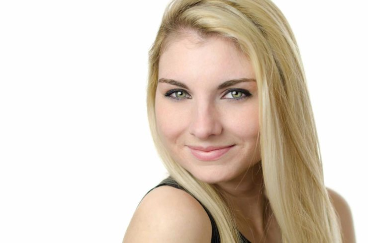 In studio acting modeling headshot portrait of blonde woman against white backdrop