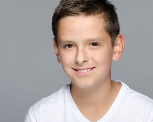 Studio modeling headshot portrait of a young boy against a grey background