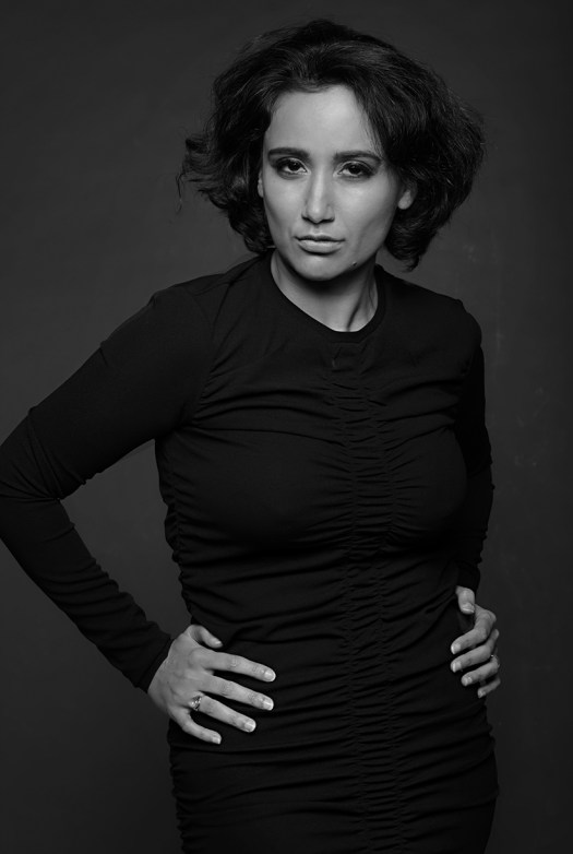 fashion-inspired portrait of a woman against a grey background