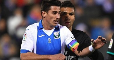 Dos jugadores uno con el brazalete de la bandera LGTB