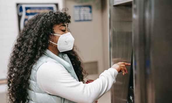 focused black woman in respirator using atm or ticket machine