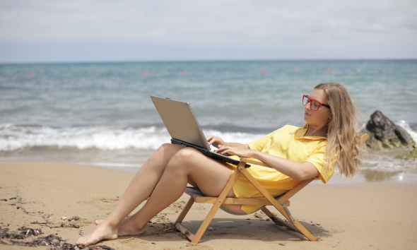 woman in yellow shirt sitting on brown wooden folding chair on beach