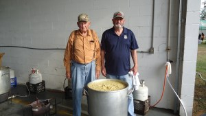 Alvan Pickels and Bo Chason stand behind a 25-gallon pot of chicken pilau at the Wetumpka Volunteer Fire Department's annual pilau supper fundraiser. PHOTO BY MAYBELLINE SOMOZA