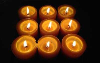 Nine beeswax candles burning