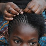 A Congolese woman braids the hair of a girl at a residence for rape victims in Goma