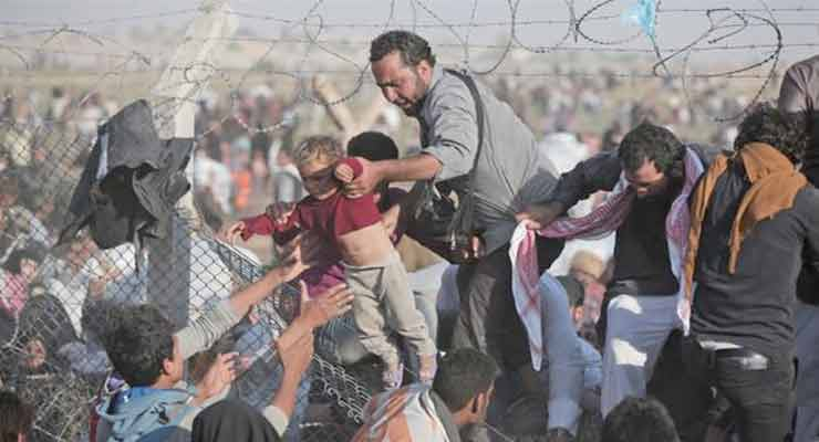 Syrian refugee trying to send an infant over a broken border fence into Turkey.