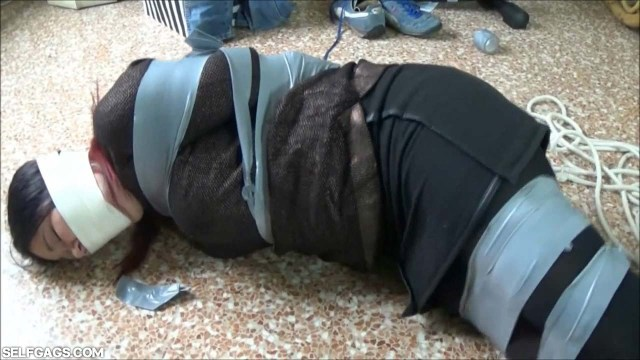 Girl tape gagged tight and bound on the floor