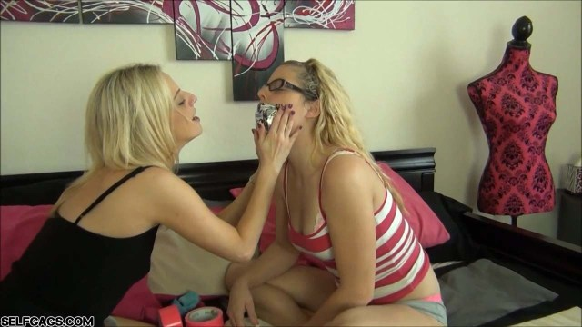 Blonde girl puts duct tape on best friend's mouth at selfgags