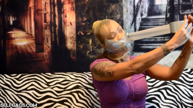 Self-gagged latina wraps duct tape around her pantyhose encased head