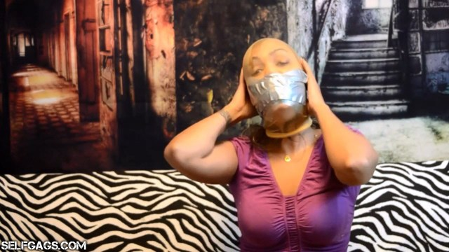 Self-gagged latina has duct tape wrapped around her pantyhose encased head