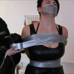 Black haired woman tied up and tape gagged with duct tape by female in leather catsuit