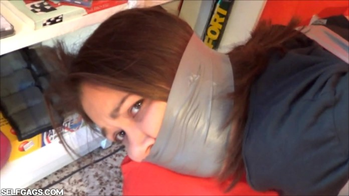 Sexy gagged gir with duct tape wrapped around the head
