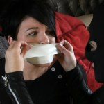 Black haired girl tape gagged by masked woman