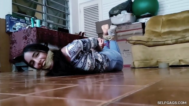 Beautiful bondage girl cleave wrap gagged with tape and hogtied on the floor in tape bondage