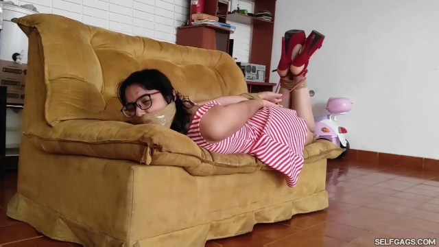 Hog tied party girl bound and gagged in high heels on sofa