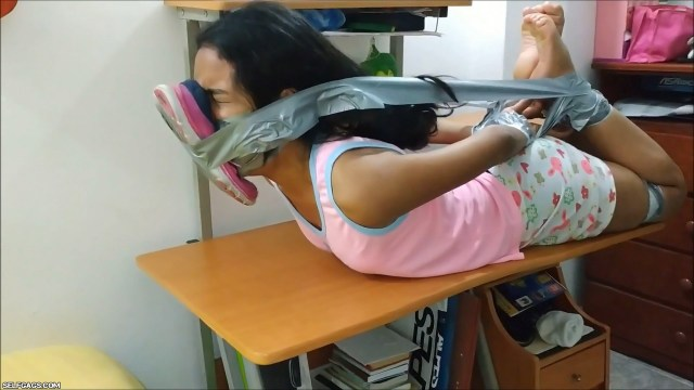 sexy latina babysitter gagged and hogtied barefoot with duct tape on table with stinky running shoe tied to her face