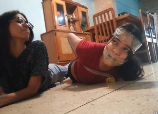 Gagged girl hogtied by girl with glasses in tight tape bondage