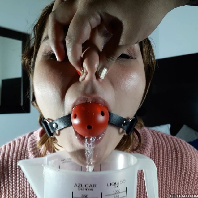 Drooling latina girl in woolen sweater has nose pinched shut while gagged with red ball gag