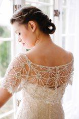 Bride in her wedding dress by a window