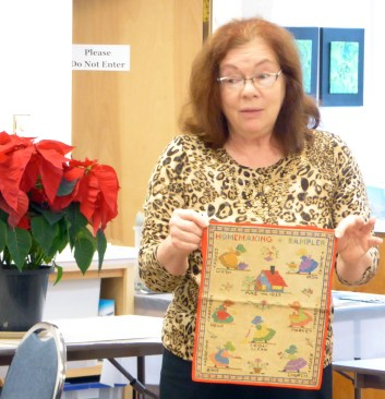 Mary shows a sampler from her family. it's about the activities of an American house wife in the 30s.