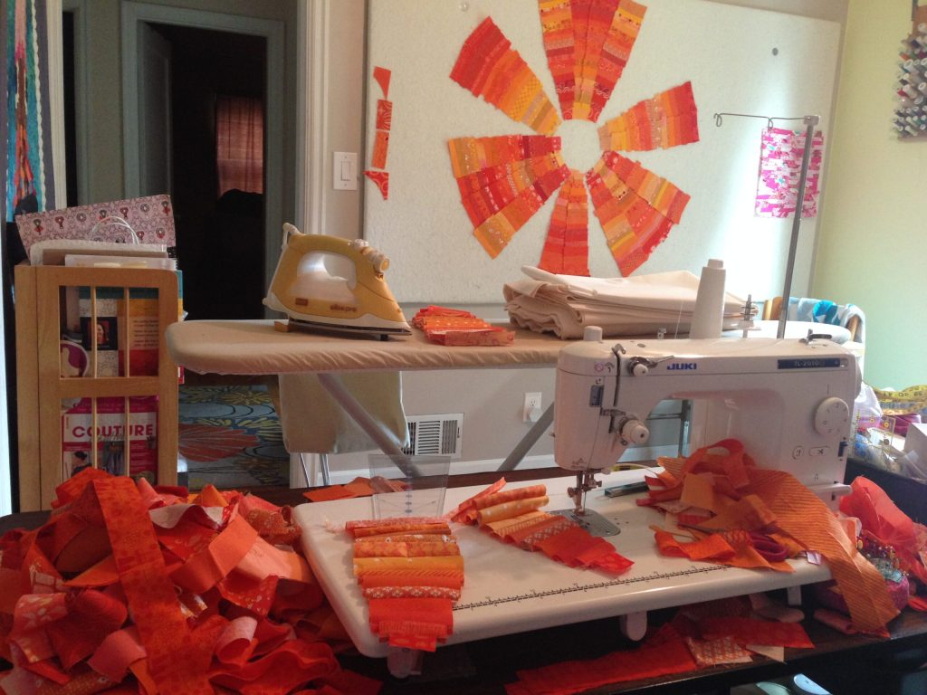 Orange fabric wedges on design wall