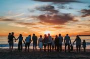 Extended family at the ocean's edge at sunset.