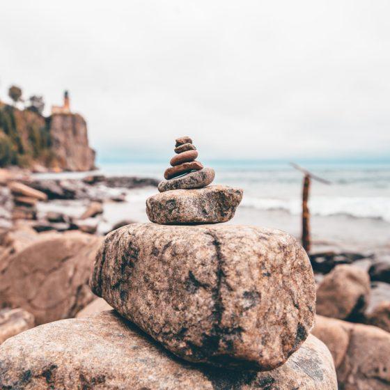 ulożone jeden na drugim kamienie, w tle zamazany morski brzeg