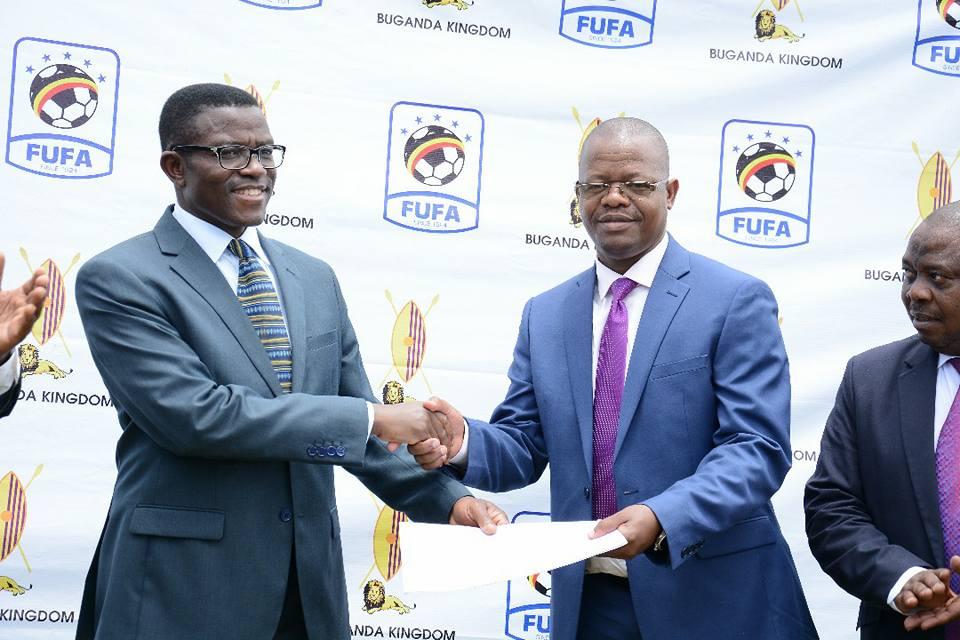 Buganda Prime minister, Mayiga (L) handing a land title to FUFA president, Magogo