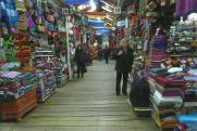Mom shopping back in Cusco, the rainbow flags are actually the symbol for the city of Cusco, representing the 4 quarters of the Incan empire