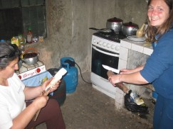 Andrea and Marysabel peeling yuka to go along with the tasty pig, Micha..