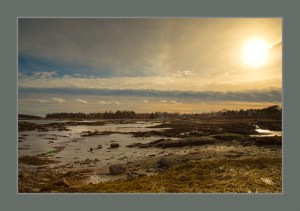 Tidal flats in winter at sunset. Mid-Coast Maine Bay. Blue and gold color tones.