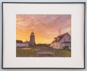 Monhegan Lighthouse at Dawn with buildings and bench against purple and orange morning clouds. June 2019.