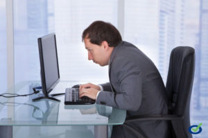 Side view of concentrated businessman working on computer at desk in office