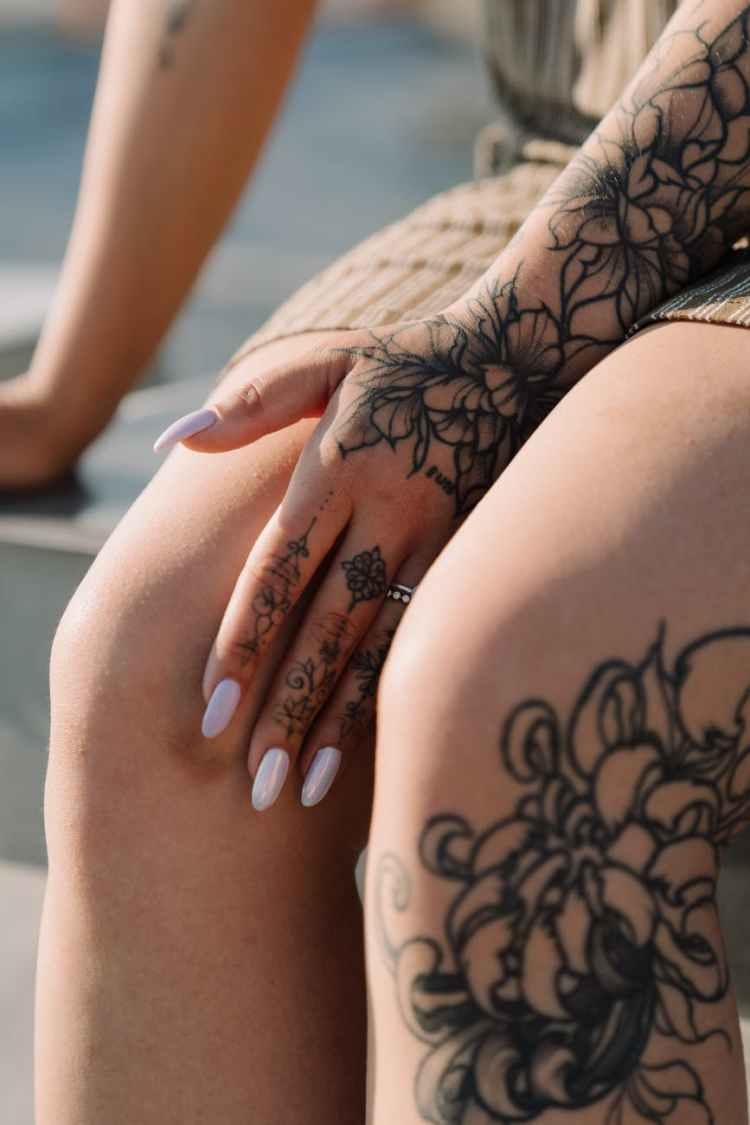woman with black floral tattoo on her left leg