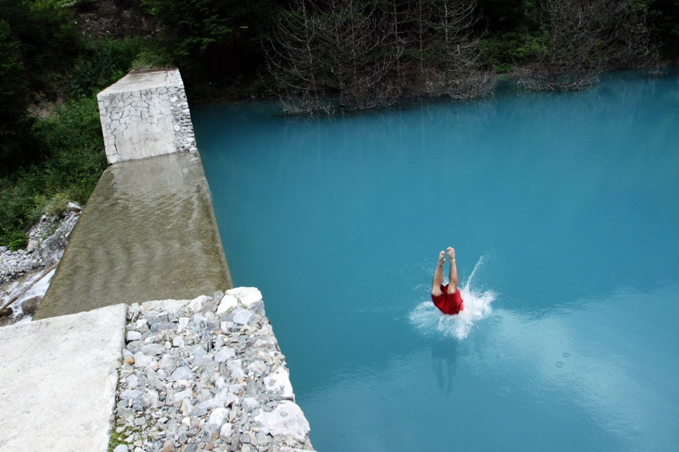 A man jumps into one of the many turquoise lakes that can be found in the Jiuzhaigou park.
