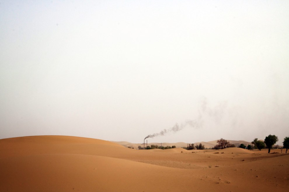 Smoke bellows from a lone factory in the deserts of western Inner Mongolia.