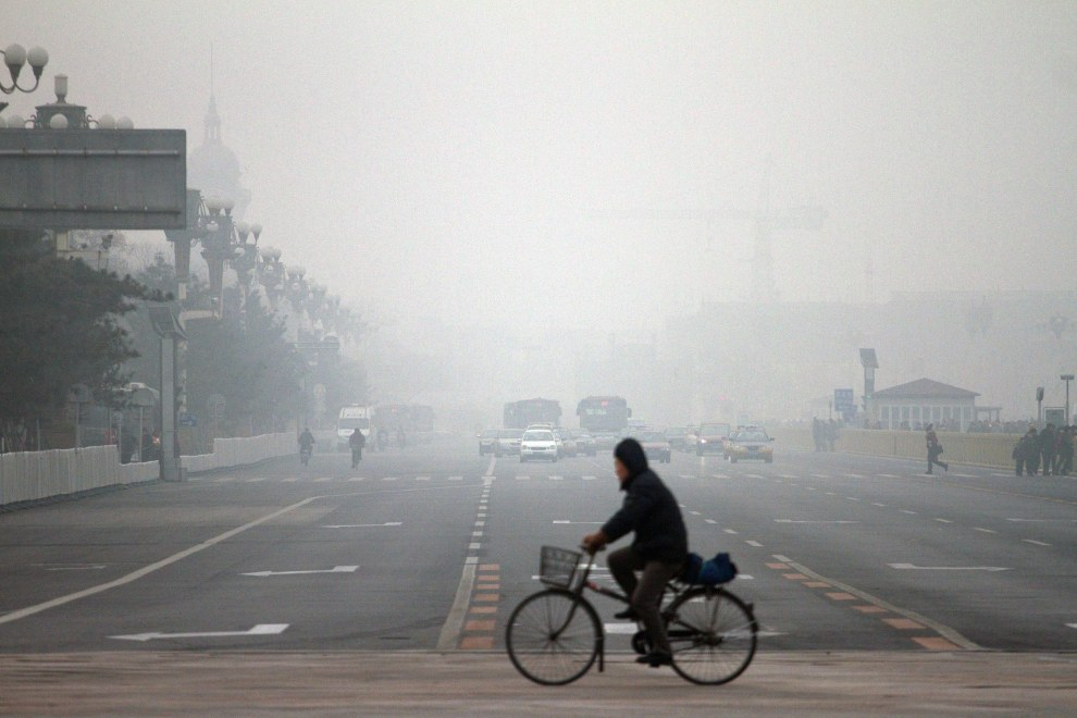 A cyclist passes Tiananmen Square on a heavily polluted day in the capital.