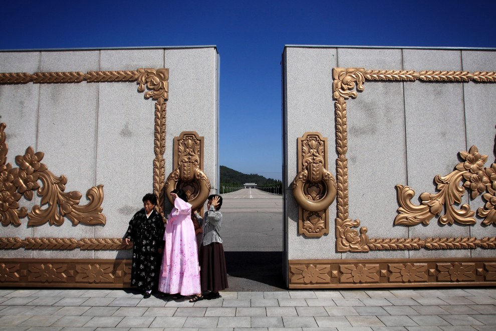 North Koreans stand near an elaborate gate in the grounds of the Kumusan Memorial Palace which houses the embalmed bodies of Kim il-Sung and Kim Jong-il.
