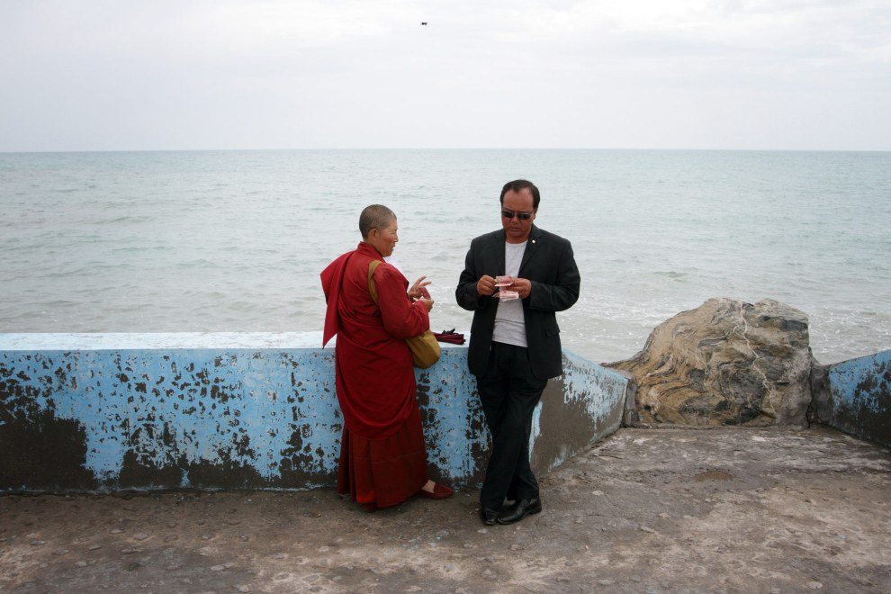 A female Tibetan monk and a Han businessman conduct a transaction near Qinghai Lake. Relations between the two ethnic groups in the west of China are historically tense.