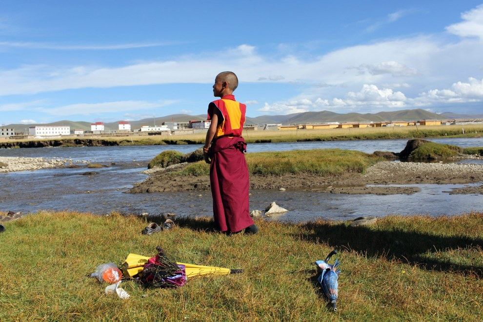 A young Tibetan monk stands next to a river in the town of Sershul in Sichuan Province.